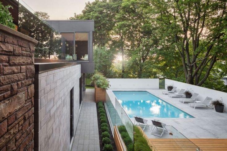 jardin avec piscine classique enterrée avec plage en béton et chaises longues