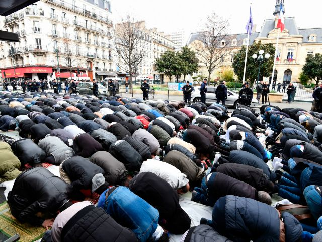 Hemmed in and closely watched by police, hundreds of Muslims have unrolled rugs and mats and prayed outdoors in the busy streets of a Paris suburb to protest the closure of their prayer hall.