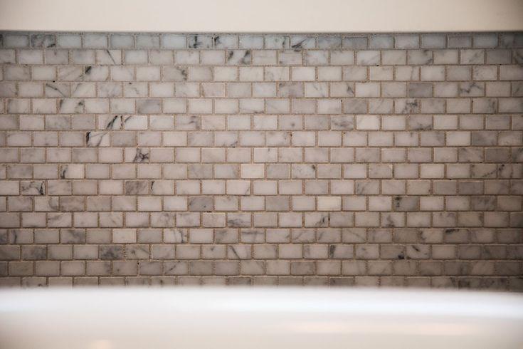 MATERIALS Bathtub Wall, Vanity Backsplash, and Shower Wall Deco | Akdo Mini Brick Carrara Mosaic Countertop | Statuary Vein Honed Italian Marble Floor | Artistic Tiles' Palisandro Bluette Tile Shower Walls | Thassos Marble 3x6 Herringbone PROJECT NOTES Every detail was consid