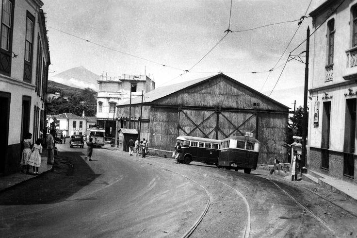 """La Estación del Tranvía en la década de 1950.  Al fondo, el café de Don Juan Morales. Al lado del tranvía, la churrería. A la izquierda, la farmacia y el surtidor de Texaco. En el centro de la imagen vemos dos guaguas """"del Valle"""" que comunicaban Tacoronte con Valle Guerra y Tejina. A la derecha, el """"Hotel Rosa"""" en cuya fachada se distingue la cartelera del """"Cine Metropolitano"""" que aún permanecía abierto en aquel entonces (Fotografía de Francisco Dávila Santana)"""