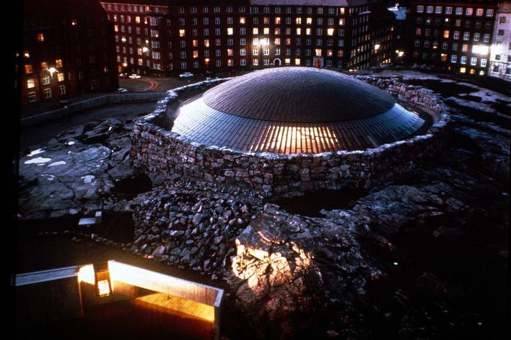 Timo i Tuomo Suomalainen, kościół Temppeliaukion, 1969, kościół wykuty w skale, całość pokryta świetlikiem, spłaszczona kopuła, niezła akustyka, fragmenty skały są ścianami, charakter katakumb, skała oprawą przestrzeni, żebra kopuły -żyletki/gigantyczna żaluzja