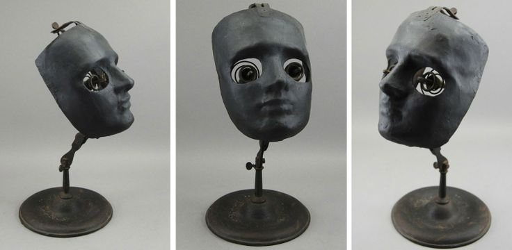 """The""""Whole Face Ophthalmophantome"""" was an instructional device used circa 1900 by ophthalmology students to hone their surgical skills.  The adjustable model consists of a black painted composition mask on brass linkage with adjustable clamps mounted to a round iron base. Two spring mounted brass eyeholders with pincers would hold pig eyes for future ophthalmologists to practice their craft before operating on human patients."""