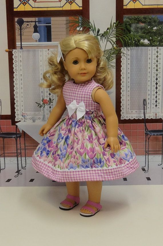 Beautiful sleeveless dress in a lovely purple tonal tulip cotton print with silver accents. The bodice is fully lined and features a contrast band in matching orchid gingham cotton adorned with white rick rack. The skirt is gathered at the waist and also features a contrast band of
