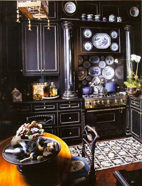 thefoodogatemyhomework:        The epitome of an un-white kitchen. Country comfy meets black drama in the city. Obsessed with the engaged columns, the black and gold Viking (a not so secret desire of mine), and the black grounded wallpaper covered in a blue and white china print which compliments the pieces of Delft around the kitchen. Don't miss the hint of a golden birdcage-type lantern above.