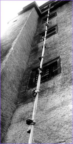 Polish Lieuts. Niki Surmanowicz and Mietek Schmiel, doing time in solitary confinement, somehow managed to get out of their locked cells and into the prison yard. Friends in the Polish quarters in floors above lowered a rope, which the pair used to get into the adjacent guardroom's attic. Putting the same rope out the attic window on the castle's western side, they began sliding down, but the nails in Schmiel's boots scraped on the wall, giving them away.