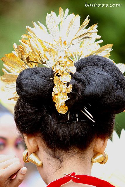 "Take a closer look to the ear ornaments of this girl, the conical ear ornaments of this girl is called ""subeng"" in Balinese language. It is usually made of gold or silver. Subeng is an ear ornament that is worn only by woman. In the old days the ears of Balinese women usually has a big hole in the place where the earrings are usually worn to accommodate the use of subeng but nowadays, Balinese craftsmen have made a subeng that can be worn without causing a big hole on the ears."