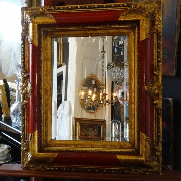 Geslepen spiegel in lak rode lijst met vergulde ornamenten
