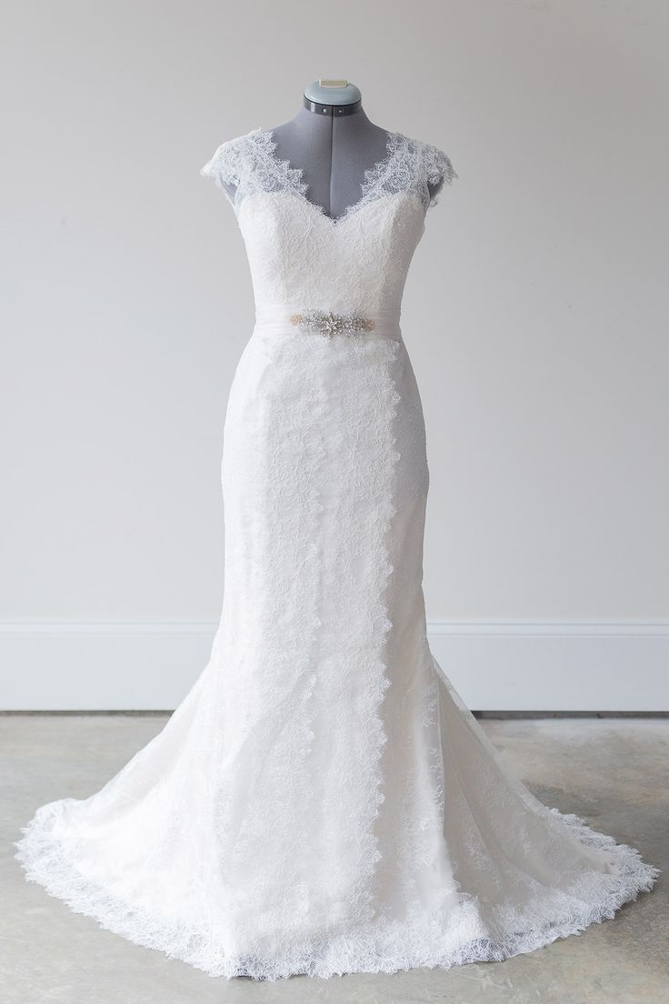 """Amy Kuschel - Rita - Amy Kuschel's trumpet Rita gown exudes elegance and glamour with its flattering silhouette, """"Heirloom English Rose"""" lace, cap sleeves, and waistline with a silk organza sash and brooch."""