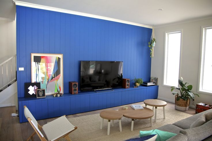 A vibrant and bold living room feature making that feature wall and TV cabinet one in the same