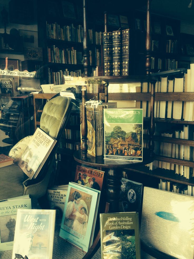 Front window of vintage book shop with old furniture to add nostalgic charm.