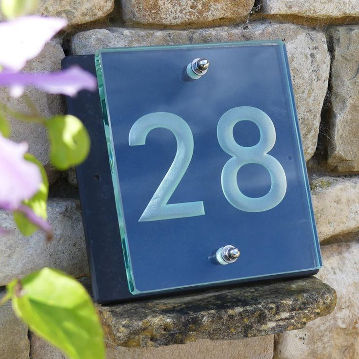 Buy our hand-crafted glass house number sign for your home or property. 15mm thick glass mounted on slate with stainless steel fixtures.