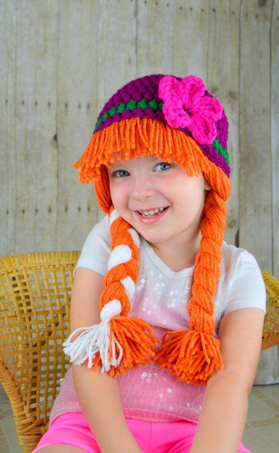 Prinzessin Anna inspiriert Hut für Halloween-Kostüm!  • Handgefertigt mit 100 % Acrylgarn • Garn ist sicher in eine gemütliche passende Mütze eingewoben. • Warm und gemütlich • Langlebig-egal wie hart Baby zieht, das Haar wird nicht kommen! • Kann auch als ein Kostüm oder ein Winter-Mütze  Dieses Design wurde inspiriert von Prinzessin Anna von Frozen. Die Mütze ist ein dunkles Magenta/lila und ist mit einem dunklen grünen Streifen und einer handgenähten Blume akzentuiert. Die Zöpfe sind…