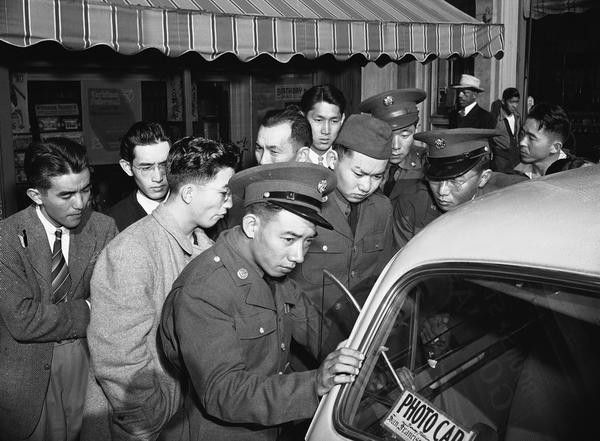 Young Japanese Americans, including several Army selectees, gather around a reporter's car in the Japanese section of San Francisco, on December 8, 1941.