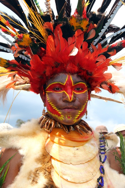 A Chimbu woman wearing her colourful headdress made from bird of paradise feathers and her shell necklace, Goroka show, PNG by Anne-Sophie Pellier, via Flickr