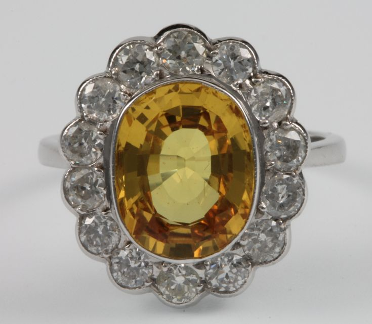 Lot 713, An 18ct white gold yellow oval sapphire and diamond cluster ring, the centre stone approx. 4ct surrounded by 14 brilliant cut diamonds approx. 1.15ct, size N, sold for £1,500