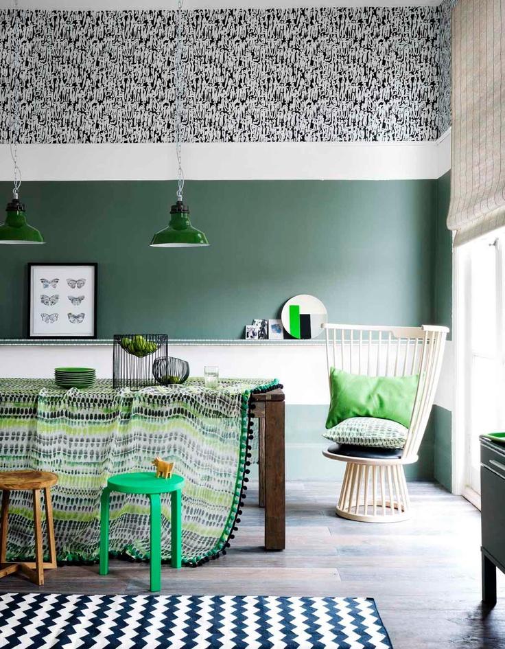 TAPET FOR KJØKKEN. Stilig med brytningene i stiler på den høye veggen. Eksotisk spisestuebord med florlett duk og lekne stoler til. Sommerlig kurvstol, blå/hvite gulvteppe og liftgardin skaper et sommerlig uttrykk.