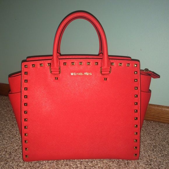 """Michael Kors ♥️ Studded Red Handbag Michael Kors large studded bright red bag with gold hardware in perfect condition, absolutely no flaws. Dimensions are 12"""" tall (with handles down) and longest across is 18"""", it is approximately 4"""" wide.  Includes shoulder strap and dust bag. Listed on mercri for$285. Michael Kors Bags Shoulder Bags"""