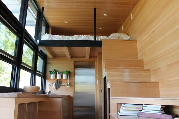 Alex Gore and Lance Cayko's finished tiny home features lots of hidden staircase storage and a wall made entirely of glass, as seen on HGTV's Tiny House, Big Living.