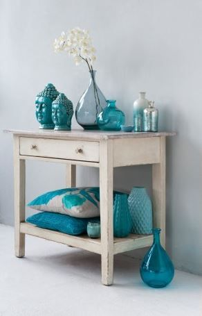 accessories artfully arranged in aqua teal turquoise. home decor design. Big mirror behind it!