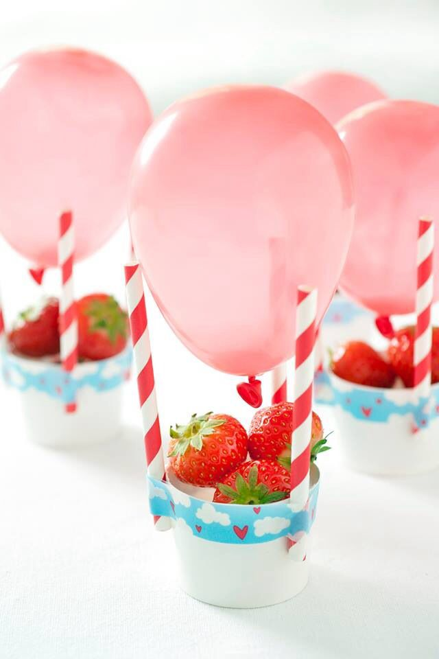 Serve up strawberries or other party nibbles in a little tub and use straws and a balloon to make a hot air balloon effect.