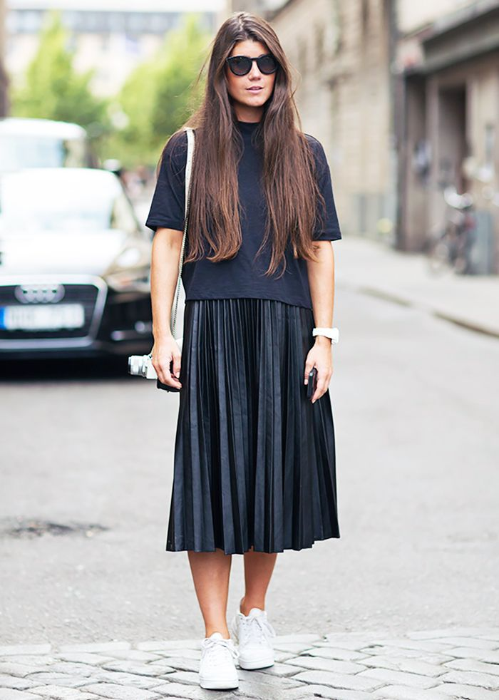 A black t-shirt is worn with a black pleated midi skirt, sneakers, and round…