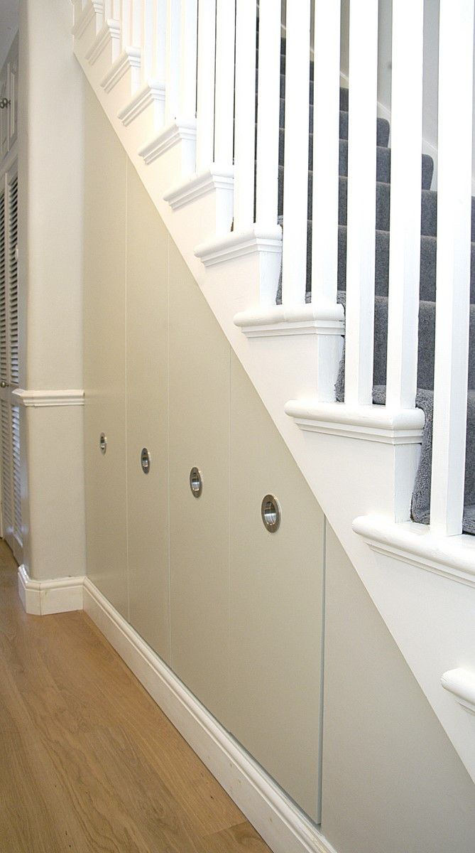 Under stairs area transformed into four pull-out shelving drawers of different heights. Contemporary simplicity blends well with traditional staircase. Doors are entirely plain except for stylish round recessed handles. Custom made under stairs storage system designed, built, painted and fitted by our expert joiners for a customer in London.