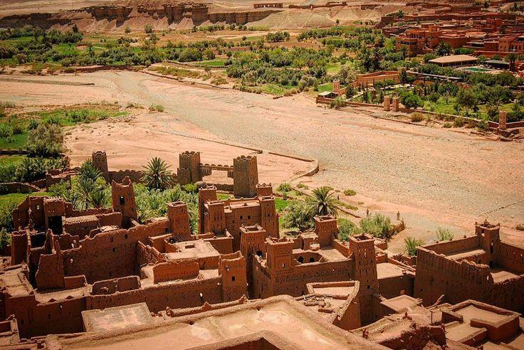 """Aït Ben Haddou es un Ksar o """"ciudad fortificada"""". Se encuentra en la provincia de Ouarzazate no muy lejos de Marrakech en la región de Souss-Massa-Draâ en Marruecos. Se extiende a lo largo del río Ounila. La mayoría de los habitantes de la ciudad viven en el nuevo pueblo al otro lado del río sin embargo algunas familias aún viven dentro del ksar. Patrimonio de la Humanidad por la Unesco desde el año 1987 este sitio que parece una maqueta en la foto esconde tal magia que ha sido escenario de…"""