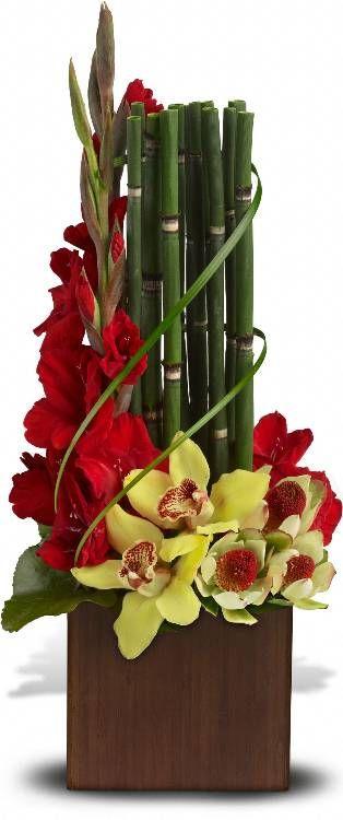 Orquídeas cymbidium amarelas, gladíolos vermelhos e leucadendron amarelo são apresentados em um vaso de bambu escuro com grama lírio, folhas de equisetum bambu e Galax.  Fotografia: Teleflora.com.