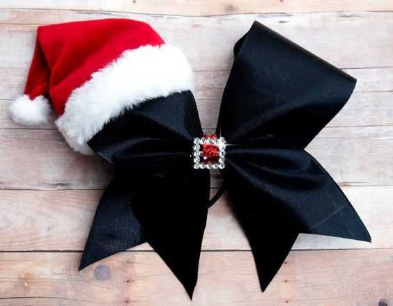 Adorable full size cheer bow with cozy Santa hat. The center is plastic so it can be worn during routines. It is attached to a hair tie. The perfect Christmas accessory.