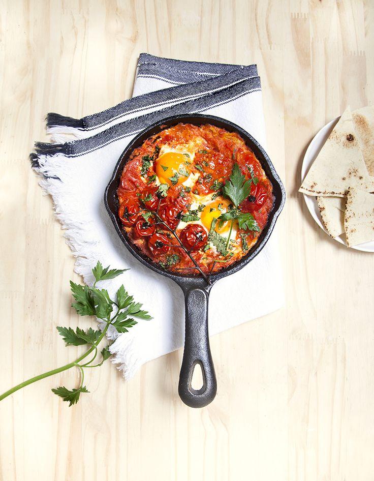 Recette Shakshuka aux oeufs et tomates : Hachez les tomates, les poivrons et l'oignon. Versez un filet d'huile d'olive dans une grande poêle (en fonte de...