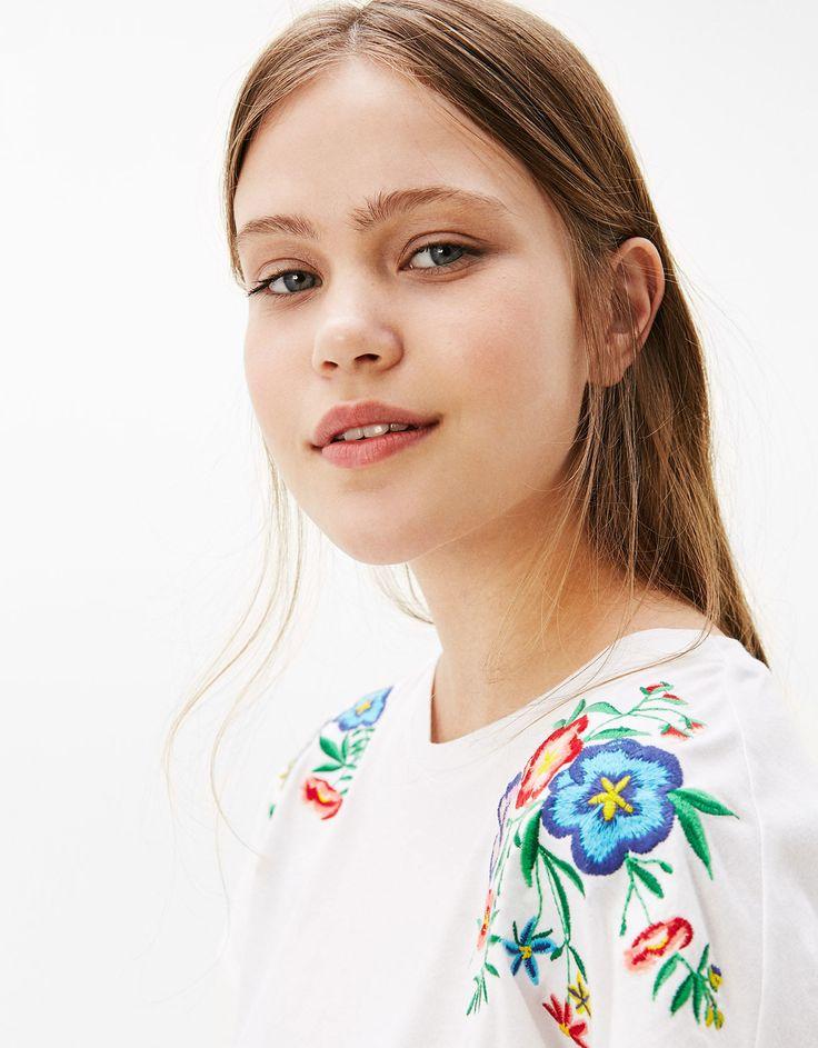 Camiseta nudo lateral flores bordadas. Descubre ésta y muchas otras prendas en Bershka con nuevos productos cada semana