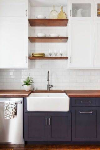 An apron front kitchen sink matches perfectly with upper white cabinets and a bit of open shelving.