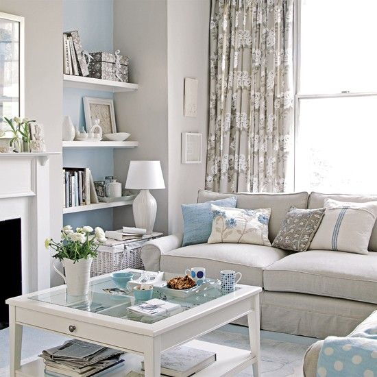 Pastel blue and gray living room has narrow shelves in niche next to fire place - Ideal Home