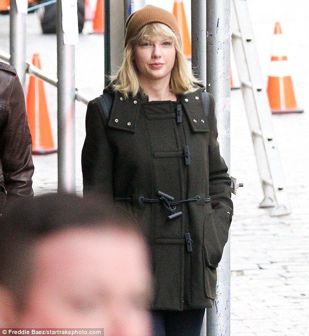 Golden: Taylor covered up in a deep green jacket featuring a black belt and oversized pockets