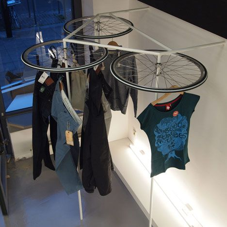 Glore Store by markmus and Neoos: Garments hang from the recycled parts of four bicycles inside a sustainable clothing shop in Stuttgart.