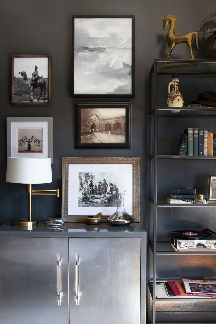 """Take a shot in the dark """"A deep, glossy paint, such as Benjamin Moore's Westcott Navy, can really play up the density of a space,"""" says Norris. """"Light-color art and accessories, by contrast, create an open and airy feel that balances out the darkness."""""""
