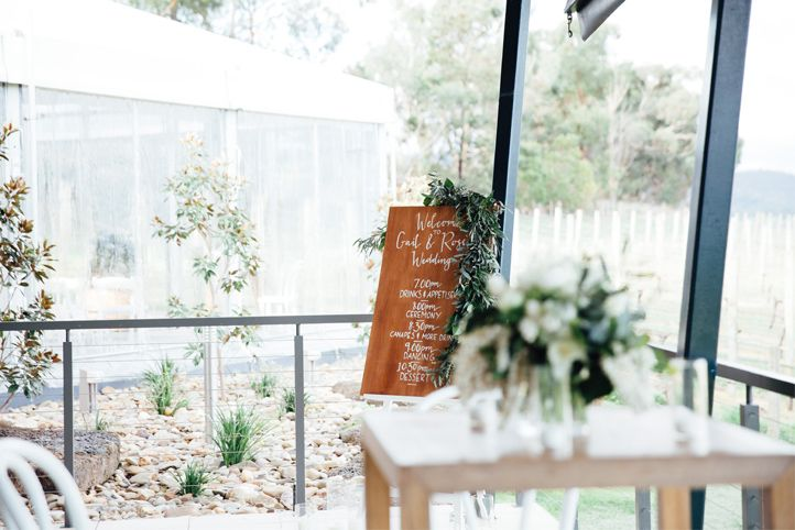 LETTUCE & CO - STYLE. EAT. PLAY 'gail + ross - winery wedding'. outdoor deck styling with a view of the vineyard. bar tables. calligraphy order of events on wood. crisp white and greens. modern refined & restrained rustic styling at Balgownie Estate Winery in the Yarra Valley.