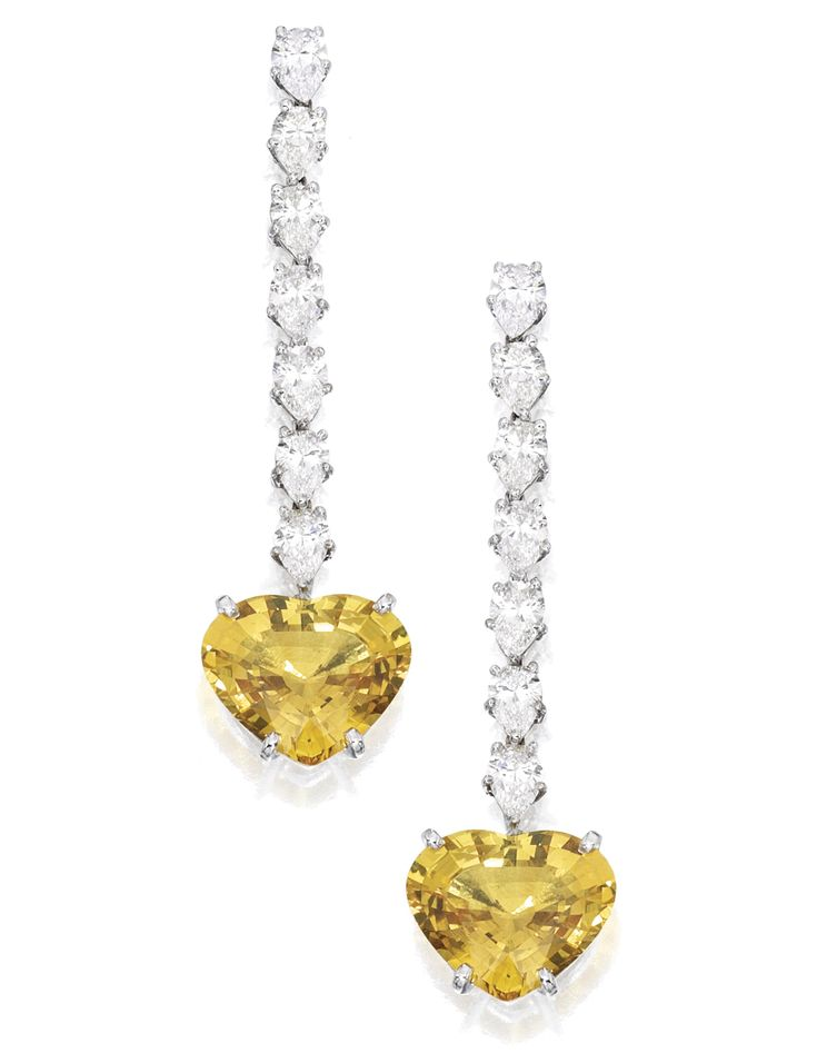 PAIR OF 18 KARAT WHITE GOLD, YELLOW SAPPHIRE AND DIAMOND EARRINGS, BULGARI. Set with two heart-shaped yellow sapphires weighing approximately 9.75 and 9.50 carats, suspended by 14 pear-shaped diamonds weighing approximately 4.45 carats, signed Bulgari.