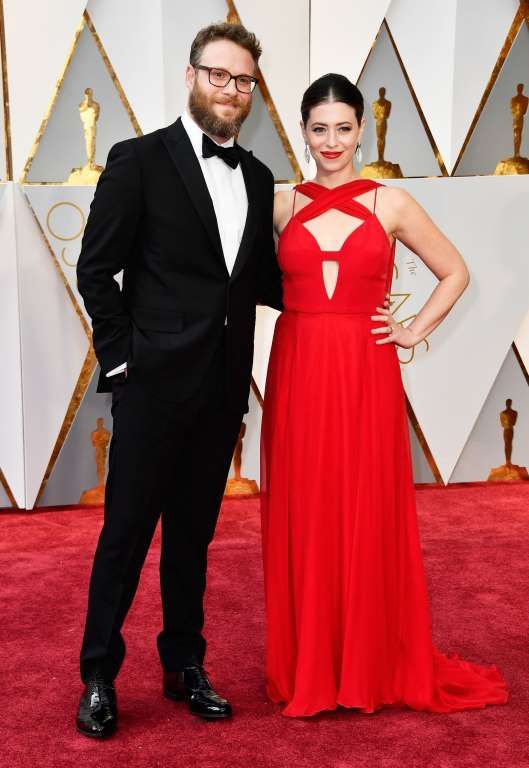 2017 Oscars red carpet:     Husband and wife Seth Rogen and Lauren Miller wore red and  black.