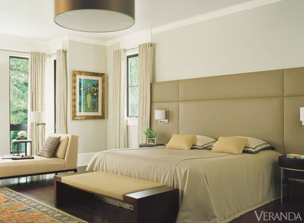Taking a cue from the owners' art collection the designer introduced coral to perk up the neutrals.Headboard in Holly Hunt leather and bedding, both by LID Casa. Sconce by Boyd Lighting. Drapes in Schumacher wool. Holly Hunt floor lamp and daybed. Cundo Bermúdez art. Artefacto bench. Luminaire ceiling fixture. INTERIOR DESIGN BY CELIA DOMENECH   - Veranda.com
