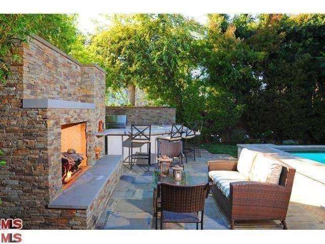 Outdoor living area with pool, spa, outdoor fireplace, pizza oven, built in BBQ station with eating area.