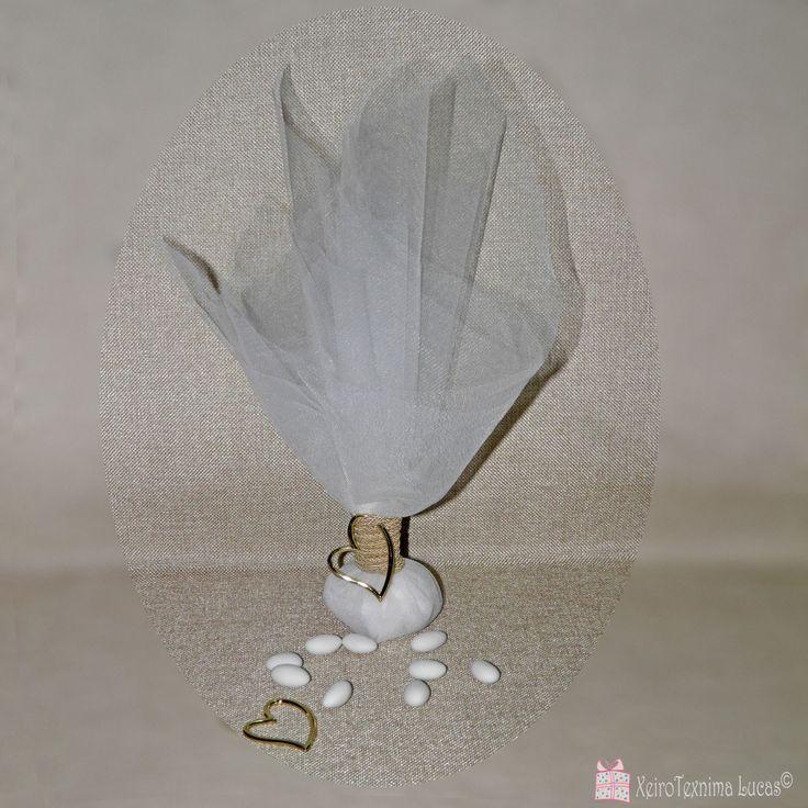 Μπομπονιέρα γάμου από λευκό τούλι, δεμένη με χρυσό κορδόνι και διακοσμημένη με μία μεταλλική καρδιά σε χρυσό χρώμα.