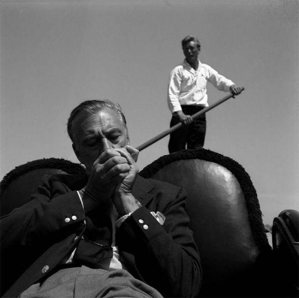 Venice, 1955.Hollywood legend Gary Cooper, on a venetian gondola, lighting a cigarette, the gondolier behind him.