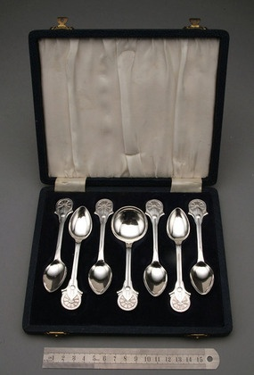"""Voortrekker Monument Silver Spoon set (7) - WH Coetzer A set of 6 teaspoons & matching jamspoon in original box, designed to commemorate the inauguration of the Voortrekker Monument in Pretoria on 16 December 1949. The front of the spoons have the Boer oxwagon wheel & powder horns, along with the Zulu shield & assegaai (spear). The rear has an outline of the Voortrekker Monument, with inscription """"1949 SVK UWB"""". These spoons are good quality, with cast design. SVK stands for..... Antique…"""
