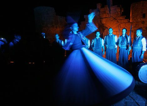 "Syrian whirling dervishes perform during the ""suhur,"" the meal before sunrise during the fasting month of Ramadan, at the historical citadel in the southern Lebanese port city of Sidon. During Ramadan, Muslims abstain from eating and drinking from dawn until dusk and spend time in prayer and contemplation."
