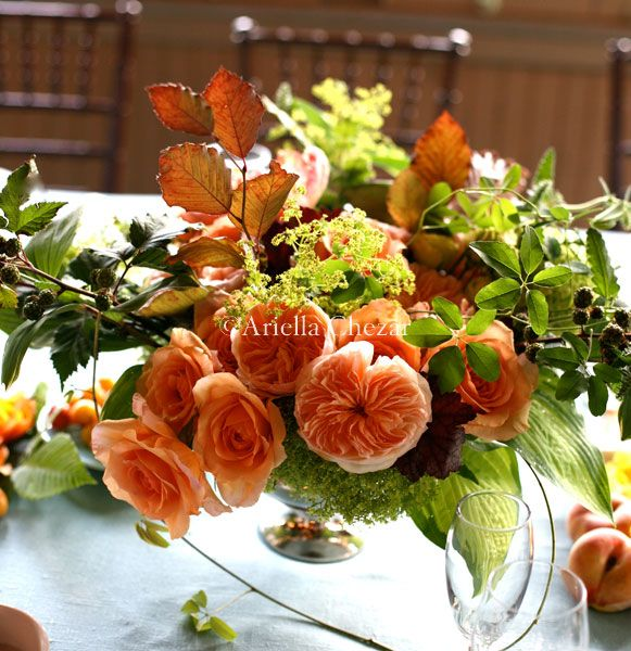orange centerpiece with roses, leaves and berries | lush flowers | in silver compote
