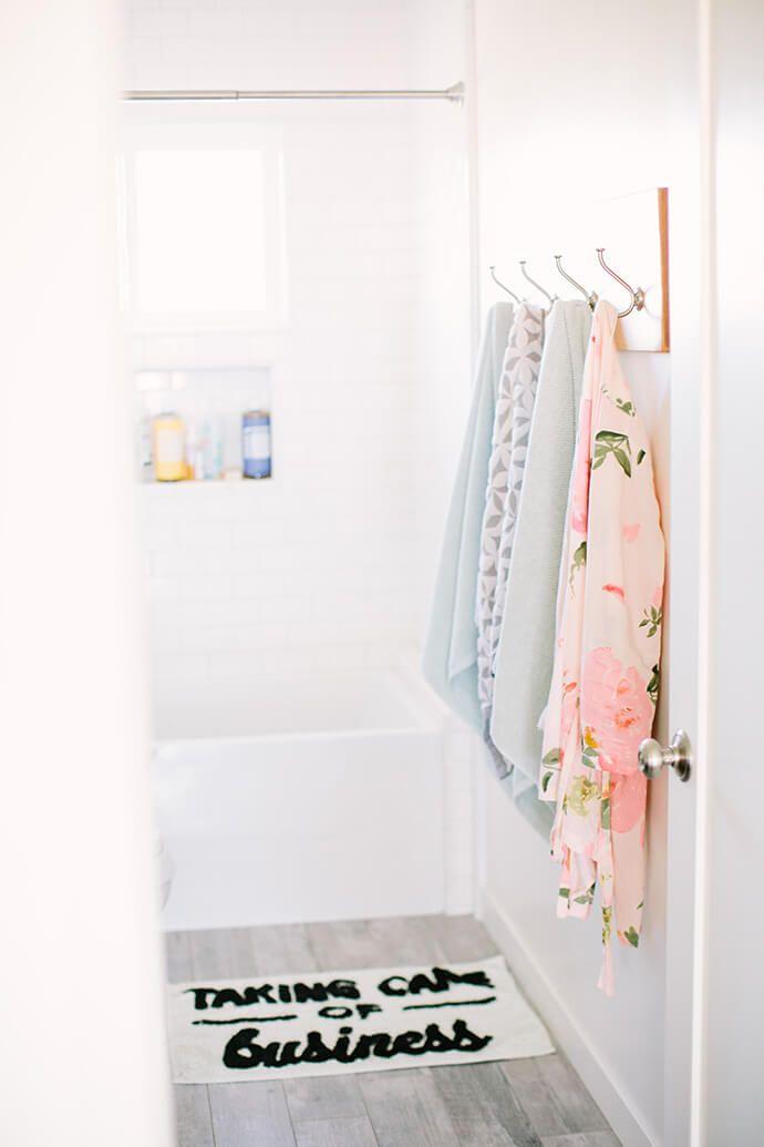 Funny bath mat in a white, airy bathroom.   Glitter Guide