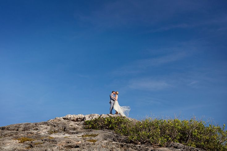 Bride & groom kiss on a cliff with blue sky. Tulum beach wedding by Quetzal Wedding Photo