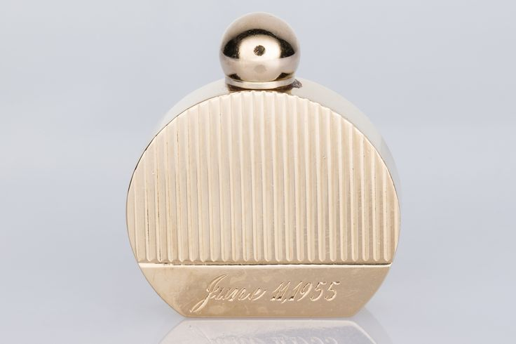 Miniature 14k perfume bottle with a hand engraved date of June 11, 1955 on the front. It's really sweet and it still works so you could carry your best fragrance around with you.  Available on www.1stdibs.com - The Jewellery Trading Company