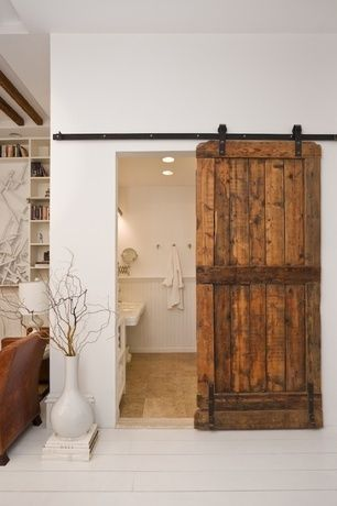 Rustic Master Bathroom with Built-in bookshelf, Barn door, Large white floor vase, Pedestal sink, Master bathroom